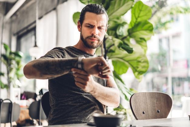 Homem bonito barbudo hipster olhando relógio com café enquanto está sentado à mesa no café