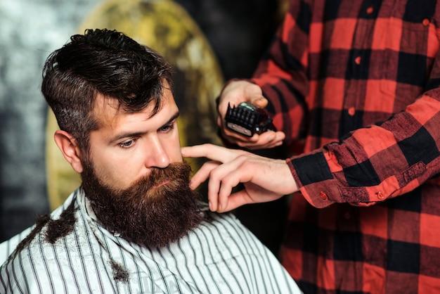 Homem bonito barbudo visitando o cabeleireiro. barbearia. hipster barbudo recebendo penteado.