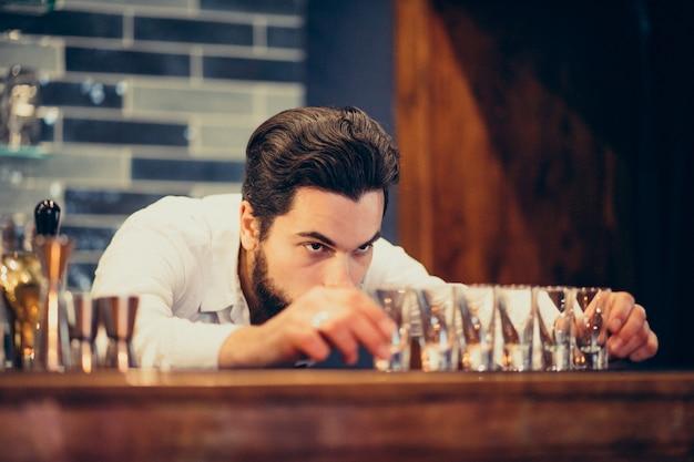 Homem bonito barman fazendo beber e cocktails num balcão