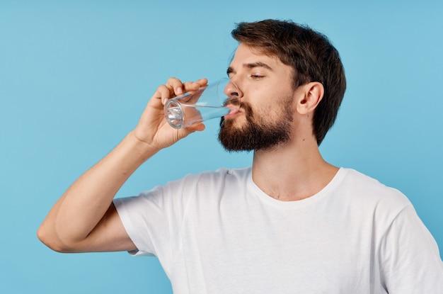Homem bonito bebendo água de um copo em um retrato de close-up azul.