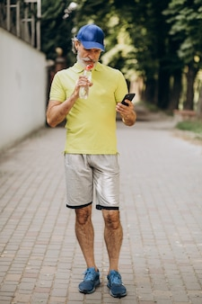 Homem bonito bebendo água no parque depois de correr