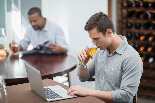 Homem bonito, bebendo cerveja enquanto estiver usando o laptop