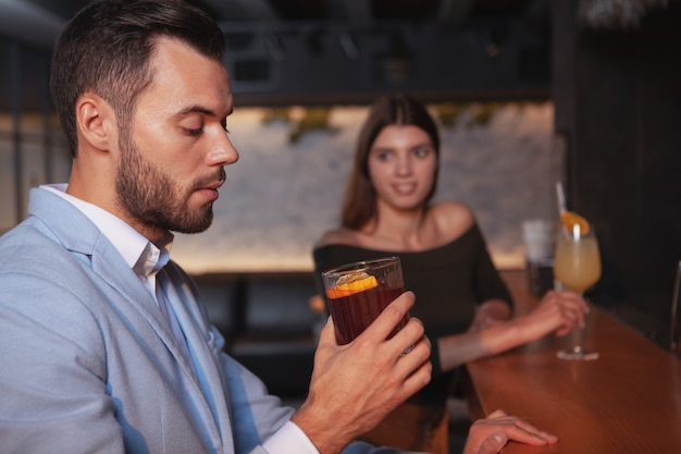 Homem bonito, bebendo coquetel de uísque, mulher olhando para ele sedutoramente