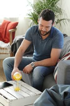 Homem bonito bebendo suco de laranja no sofá