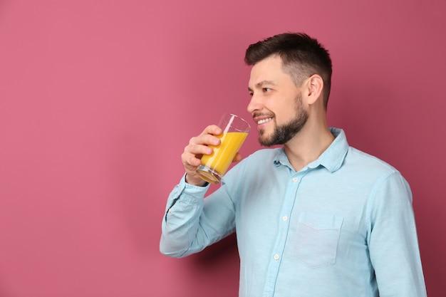Homem bonito bebendo suco de laranja