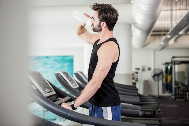 Homem bonito beber água na esteira na academia