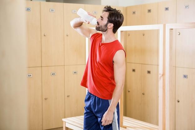 Homem bonito beber água no vestiário
