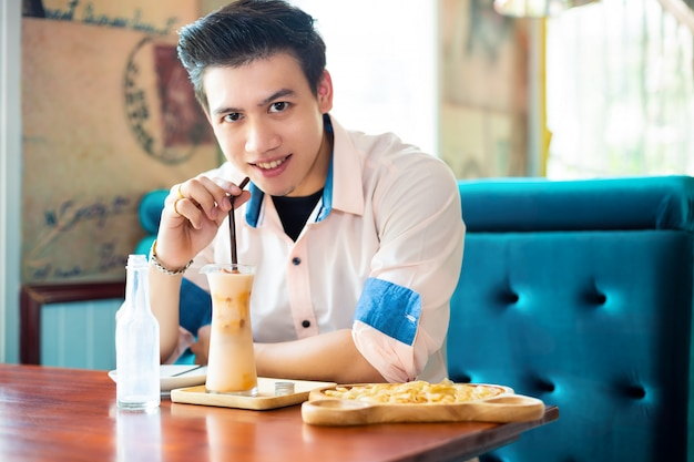 Homem bonito beber chá gelado no café
