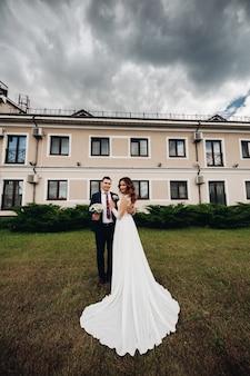 Homem bonito beija sua linda esposa e segura seu buquê de noiva