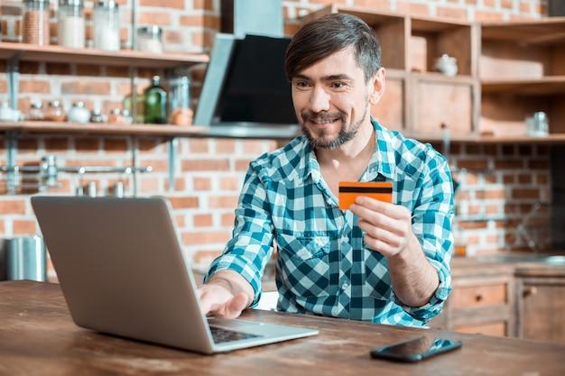 Homem bonito, bonito e positivo usando seu laptop e sorrindo enquanto faz uma transferência de dinheiro