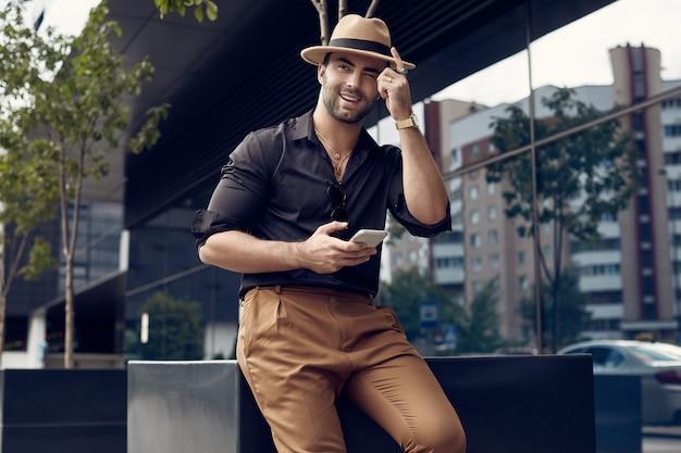 Homem bonito bronzeado hipster muscular brutal na camisa preta e chapéu com telefone