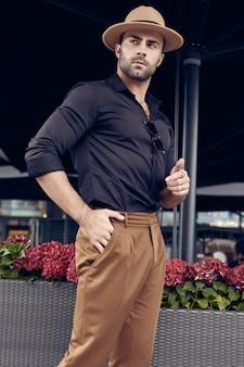 Homem bonito bronzeado hipster muscular brutal posando nas ruas