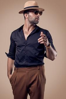 Homem bonito brutal hipster bronzeado em uma camisa preta, chapéu e óculos