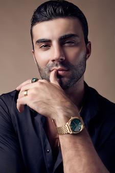 Homem bonito brutal hipster bronzeado em uma camisa preta