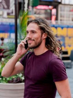 Homem bonito caminha e fala por telefone