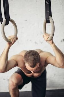 Homem bonito cansado após levantamento de peso no ginásio