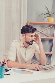 Homem bonito cansado tendo um dia difícil no escritório