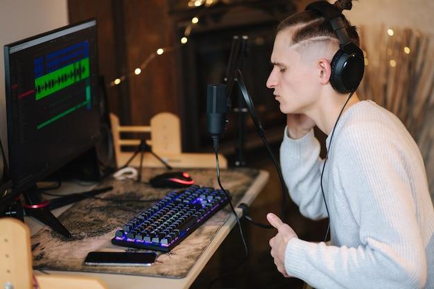 Homem bonito canta em casa pelo homem do computador usa equipamento de som profissional, como microfone e