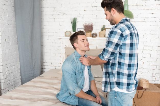 Homem bonito, carinhoso e feliz sorrindo e arrumando a camisa do namorado enquanto fica em frente a ele perto de uma cama