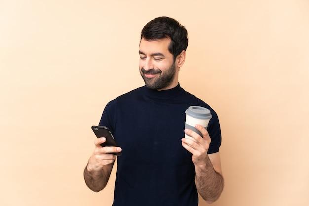 Homem bonito caucasiano ao longo da parede, segurando o café para levar e um celular