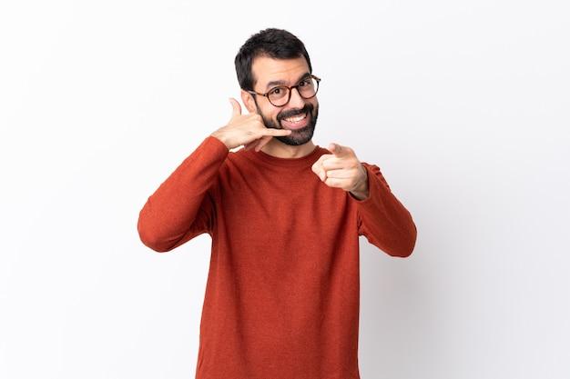 Homem bonito caucasiano com barba sobre branco fazendo gesto de telefone e apontando a frente