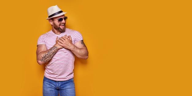 Homem bonito, caucasiano, com barba, vestindo camiseta listrada casual, sorrindo com as mãos no peito com gra ...