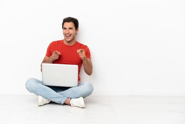 Homem bonito caucasiano com um laptop sentado no chão apontando para a frente e sorrindo