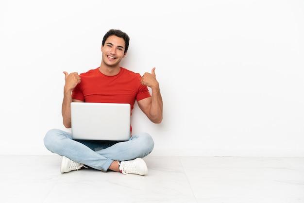 Homem bonito caucasiano com um laptop sentado no chão com um gesto de polegar para cima e sorrindo