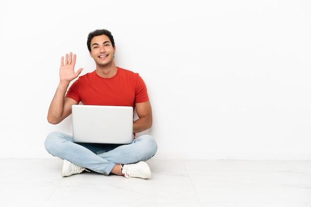 Homem bonito caucasiano com um laptop sentado no chão e saudando com a mão com uma expressão feliz