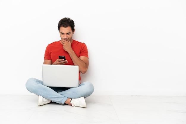 Homem bonito caucasiano com um laptop sentado no chão, pensando e enviando uma mensagem