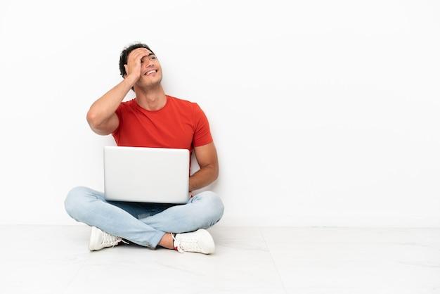 Homem bonito caucasiano com um laptop sentado no chão percebeu algo e pretendendo a solução