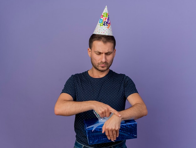 Homem bonito caucasiano descontente com boné de aniversário segura e olha para a caixa de presente isolada no fundo roxo com espaço de cópia