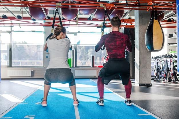 Homem bonito caucasiano e jovem aderirem à aula de trx do clube desportivo malhando no ginásio. jovem casal musculoso concentrado fazendo exercícios de resistência total do corpo interno. foto horizontal