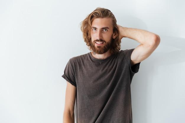 Homem bonito caucasiano em pé isolado sobre a parede cinza.