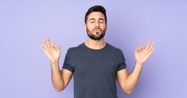 Homem bonito caucasiano em pose de zen sobre parede roxa isolada