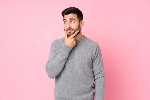 Homem bonito caucasiano em uma parede isolada, tendo dúvidas e com expressão facial confusa