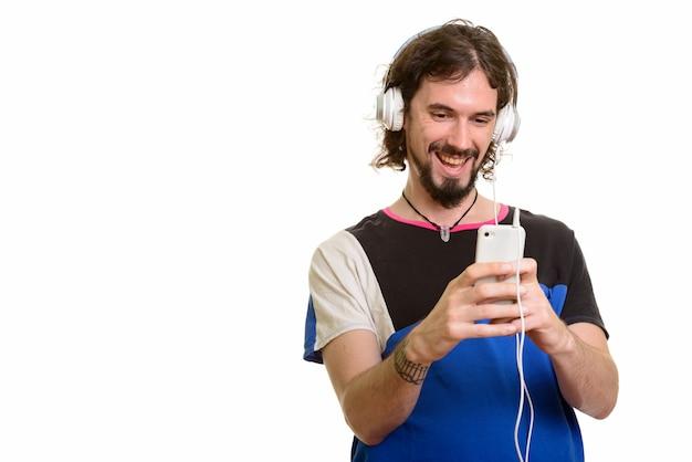 Homem bonito caucasiano feliz usando o celular enquanto ouve música