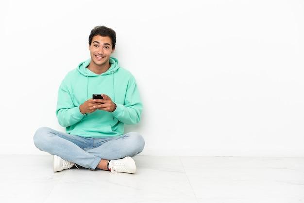 Homem bonito caucasiano sentado no chão enviando uma mensagem com o celular
