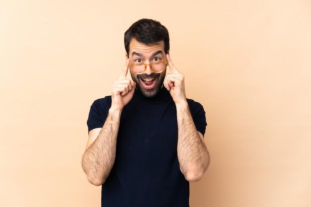 Homem bonito caucasiano sobre parede com óculos e surpreso