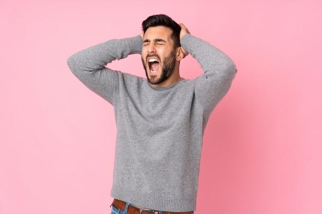Homem bonito caucasiano sobre parede estressado oprimido