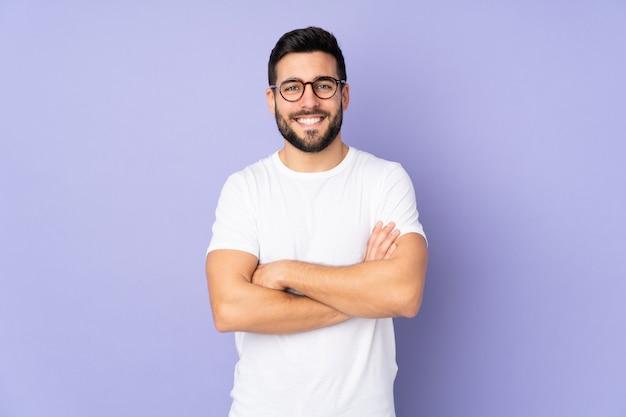 Homem bonito caucasiano sobre parede isolada, mantendo os braços cruzados na posição frontal