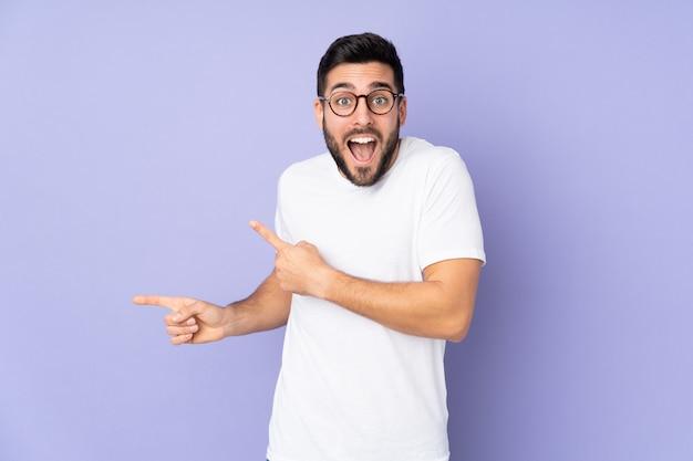 Homem bonito caucasiano sobre parede isolada surpreso e apontando o lado