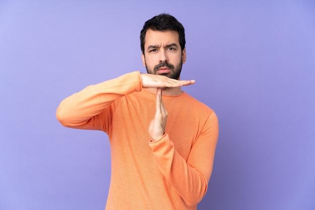 Homem bonito caucasiano sobre parede roxa isolada, fazendo gesto de intervalo