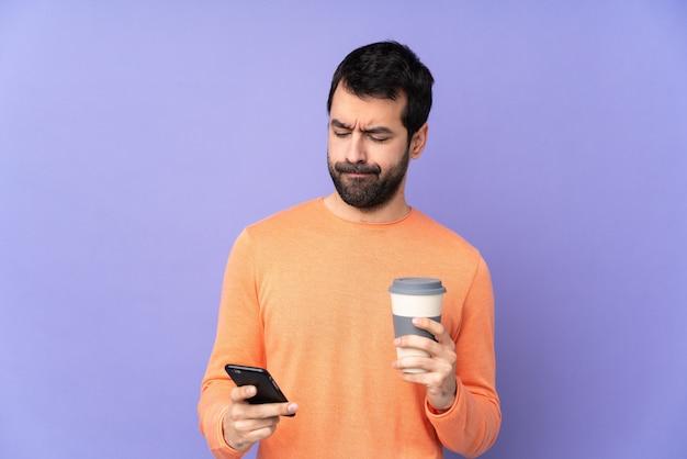Homem bonito caucasiano sobre parede roxa segurando café para tirar e um celular