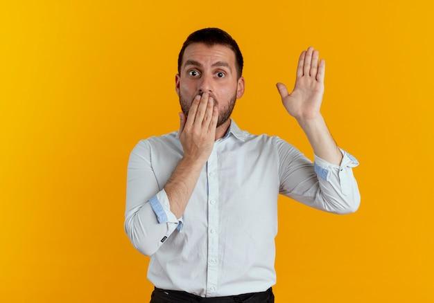 Homem bonito chocado colocando a mão na boca e levantando a mão isolada na parede laranja