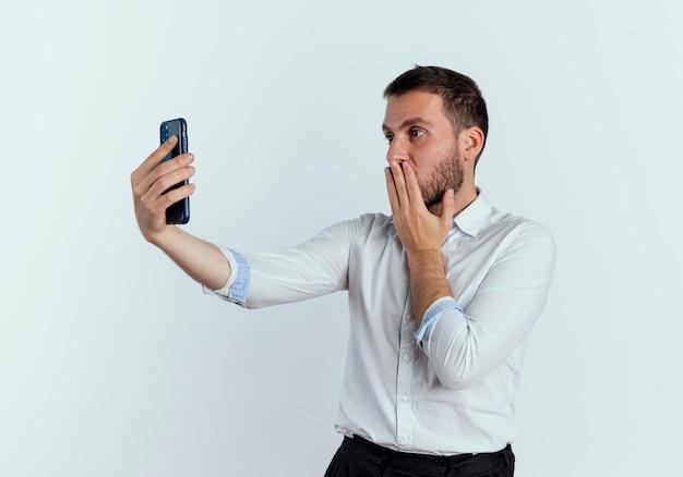 Homem bonito chocado com a mão na boca olhando para o telefone isolado na parede branca