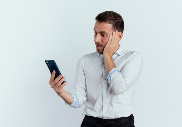 Homem bonito chocado com a mão no rosto olhando para o telefone isolado na parede branca