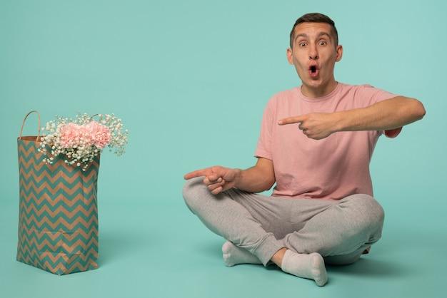 Homem bonito chocado em camiseta rosa, sentado no chão com a boca aberta, apontando para a sacola de compras com flores