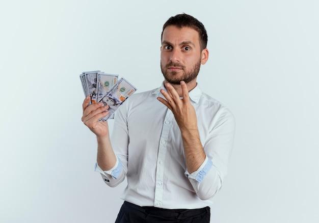 Homem bonito chocado segurando dinheiro e gesticulando quatro com a mão isolada na parede branca