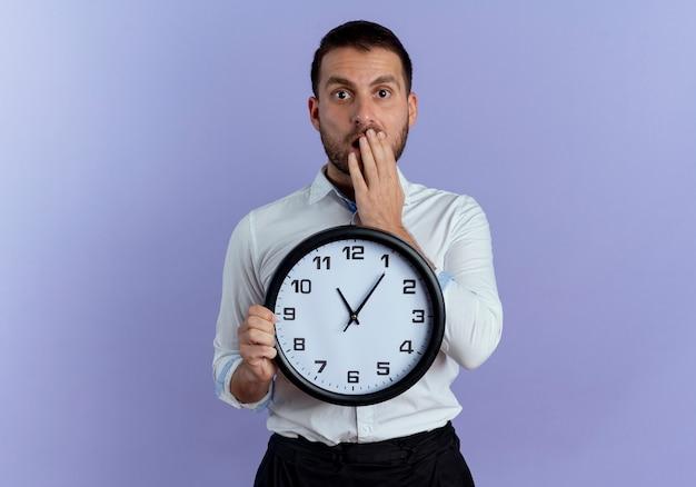 Homem bonito chocado segurando relógio coloca a mão na boca isolada na parede roxa